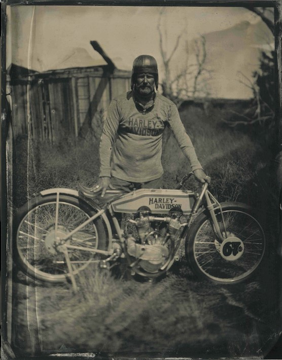 Old image of a man with an old Harley Davidson